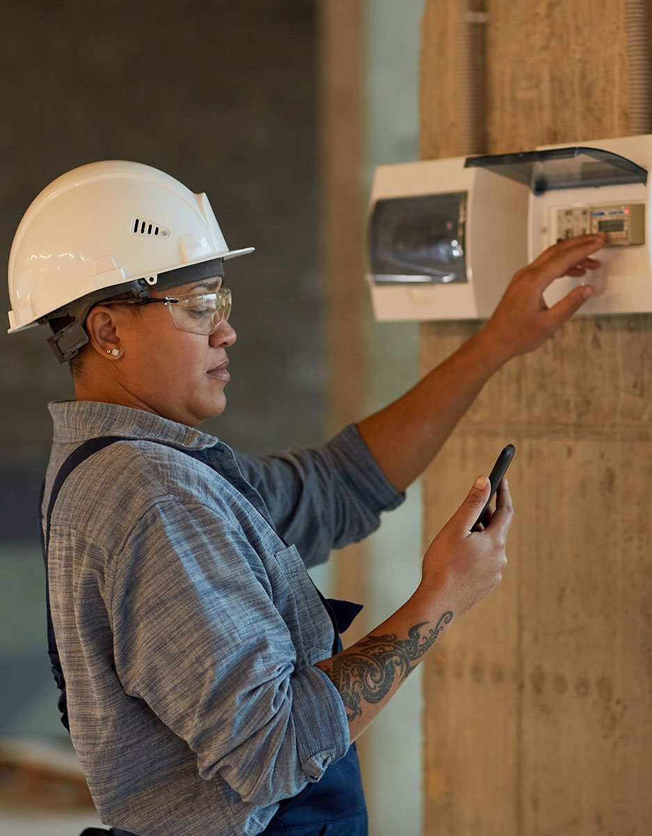 Woman With Hard Hat And Safety Goggles Setting Alarm System Looking At Phone