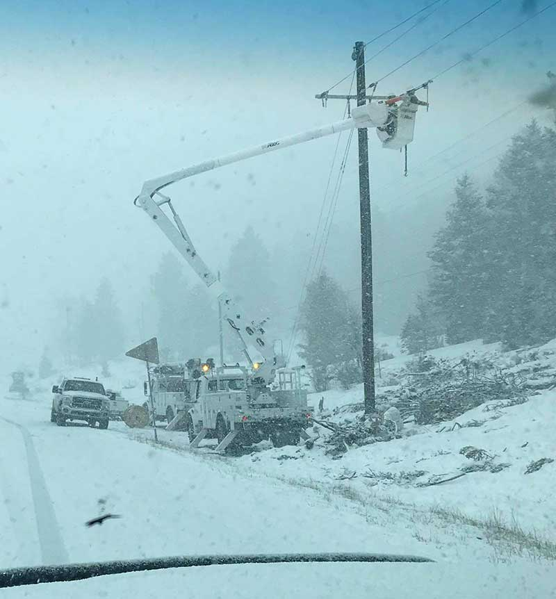Bucket Truck Repairing Electric Lines In A Snowstorm